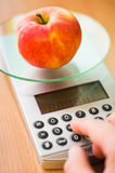 Apple on kitchen scale. Apple on digital kitchen scale - calculating calories Stock Image