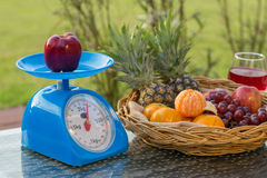 Apple on kitchen scale with fruits in basket an wine glass Stock Images
