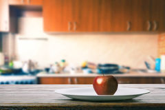 Apple on the kitchen table Royalty Free Stock Image