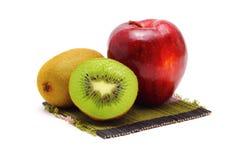 Apple and kiwi fresh fruit on bamboo. Royalty Free Stock Images
