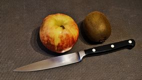 Apple, kiwi and knife royalty free stock photography