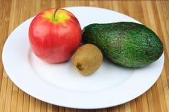 Apple, kiwi och avokado på en plätera arkivfoto