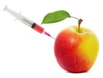 Apple klibbade med injektionssprutan, begrepp av genetisk ändring av frukter Royaltyfri Fotografi