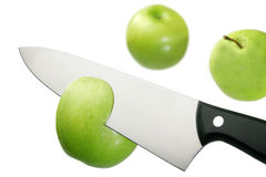 Apple and knife. Knife cutting apples . Green apples in white Royalty Free Stock Photo