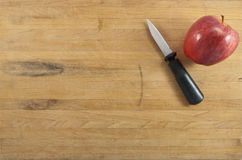 Apple and Knife on Cutting Board Stock Images