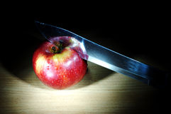 Apple and knife in the dark Royalty Free Stock Image