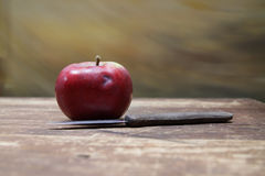 Apple and knife on a wooden table Royalty Free Stock Image