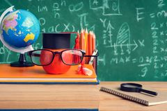 Apple Knowledge Symbol and Pencil Books on the desk with board b. Ackground.Education concept school Royalty Free Stock Images