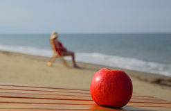 Apple and lady. Closeup of red apple against blurred background with figure of woman sitting in beach chair Royalty Free Stock Photography