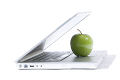 Apple Laptop. A green apple sitting on a laptop isolated Stock Photo
