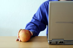 Apple and laptop. Businessman working on a laptop and holding an apple
