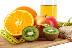 Apple, laranja, quivi com medida da fita no fundo branco fotografia de stock