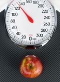 Apple laying on weight scale s. Hot from above Royalty Free Stock Photos