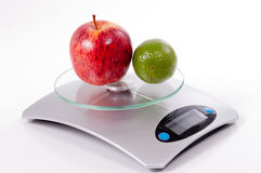 Apple and lemon on kitchen scale Royalty Free Stock Photos
