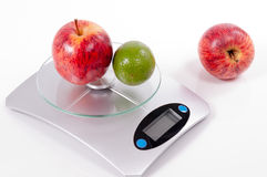 Apple and lemon on kitchen scale Stock Image