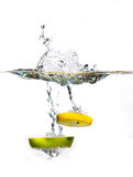 Apple and lemon slice in water. A slice of apple and lemon sinking in water together Stock Image