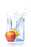 Apple and lemon in water and splashes Stock Images