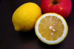 Apple and Lemons. A vivid image of an apple and two lemons Stock Images