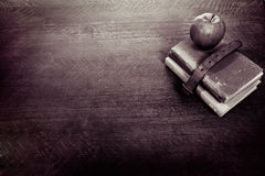 Apple, libros viejos y escritorio Foto de archivo libre de regalías