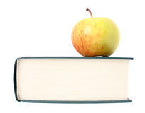 Apple lies on right side of closed book Royalty Free Stock Photography