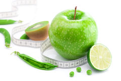 Apple,lime,peas,kiwi and measure tape Stock Photos
