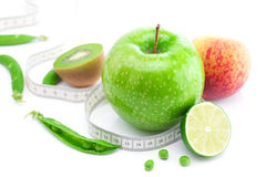 Apple,lime,peas,kiwi ,peach and measure tape Stock Photos