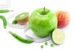 Apple,lime,peas,kiwi ,peach and measure tape Stock Photos