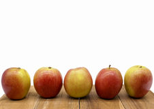 Apple line up on wood block Royalty Free Stock Photography