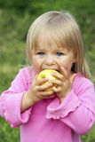 Apple. Little beautiful girl eats an Apple on a nature royalty free stock photos