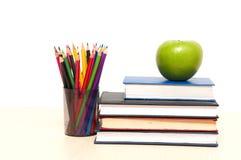 Apple, livres et crayon coloré Image stock