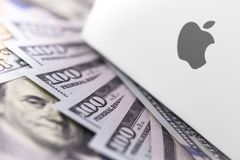 Apple logo on box, money, dollars. Apple is a multinational tech. Nology company that designs, develops, and sells electronics, computer software, and online royalty free stock photo