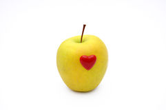 Apple love. A small red heart on a yelow green apple, isolated Royalty Free Stock Image