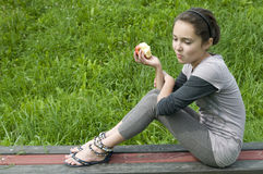 Apple for lunch. Brunette young girl on bench eating apple stock photo