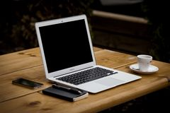 Apple Macbook Air on Wood Tabletop with Espresso Cup, Notepad, Pen, and iPhone Stock Images