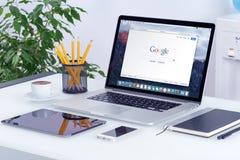 Apple MacBook Pro på skrivbordet med den Google sökandewebbsidan arkivfoton