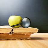 Apple and magnifying glass over the books Royalty Free Stock Photography