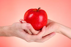 Apple between man and woman Royalty Free Stock Images