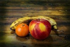 Apple mandarine och banan på träbakgrunden Arkivfoton