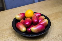 Apple mangos, oranges, and lemons in the bowl in the kitchen stock image