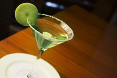 Apple Martini mixed drink with fruit slice garnish. Served on a wooden table Stock Image