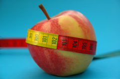 Apple with measure tape. The picture symbolises fitness, slimness and diet Stock Photo