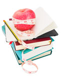 Apple with measure tape on big pile of books. Big ripe red apple with white measure tape around it on pile of books as metaphore of healthy eating and diet Royalty Free Stock Photography