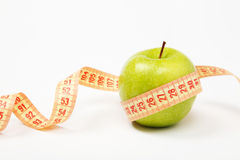 Apple and measurement tape. Measurement tape wrapped around green apple/Concept for health, diet Stock Images