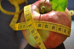Apple and measurement tape. Measurement tape wrapped around green apple/Concept for health, diet Stock Photography