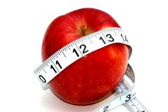 Apple and measuring tape. An apple wrapped by a measuring, a concept showing weight loss and diet stock photography