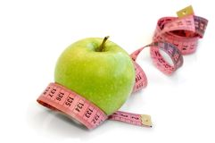 Apple and measuring tape. Isolated on a white Royalty Free Stock Photography