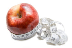 Apple with measuring tape. Apple entangled with measuring tape - abstract healthy food symbol Royalty Free Stock Photography