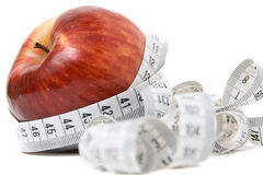 Apple with measuring tape. Apple entangled with measuring tape - abstract healthy food symbol Stock Photo