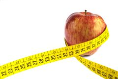 Apple and measuring tape. Apple with measuring tape around in white background royalty free stock photography