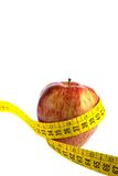 Apple and measuring tape. Apple with measuring tape around in white background royalty free stock photos